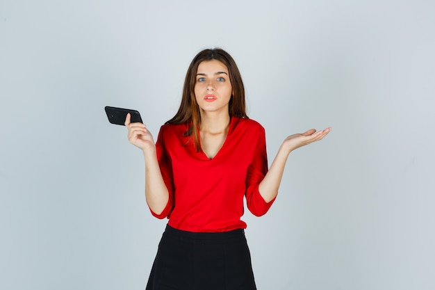 Jonge dame die mobiele telefoon houdt terwijl hulpeloos gebaar in rode blouse wordt getoond