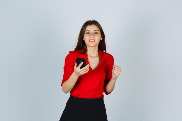 Jonge dame die mobiele telefoon houdt terwijl winnaargebaar in rode blouse wordt getoond