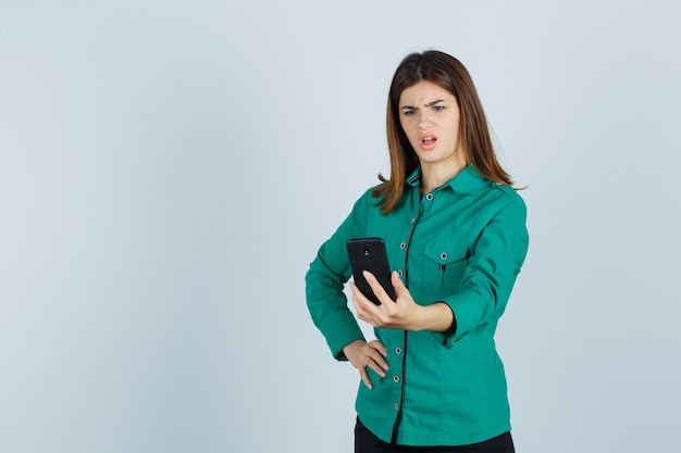 Jonge dame die mobiele telefoon in groen overhemd bekijkt en verbaasd, vooraanzicht kijkt.