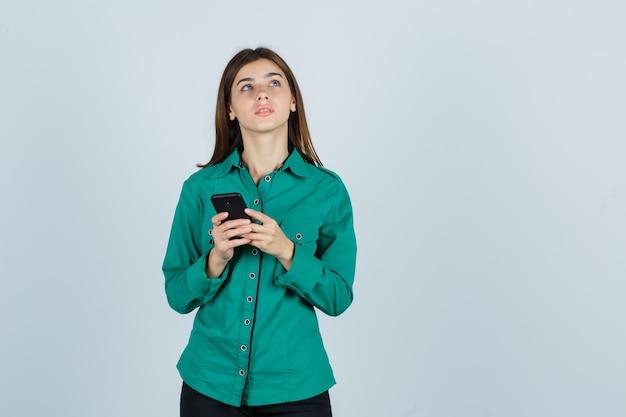 Jonge dame die mobiele telefoon in groen overhemd houdt en nadenkend kijkt. vooraanzicht.