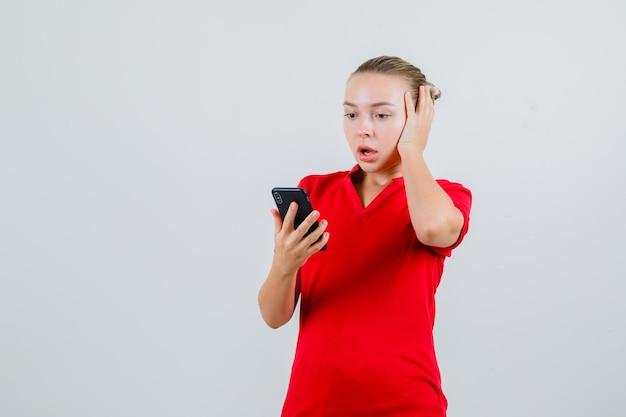 Jonge dame die mobiele telefoon in rood t-shirt bekijkt en geschokt kijkt