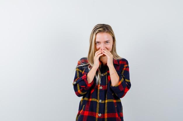 Jonge dame die mond bedekt met vingers in geruit overhemd en er schattig uitziet. vooraanzicht.