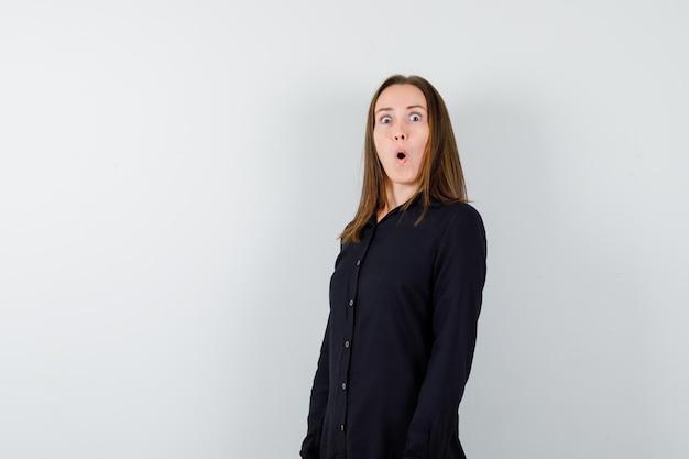 Jonge dame die mond opent en verbaasd kijkt?
