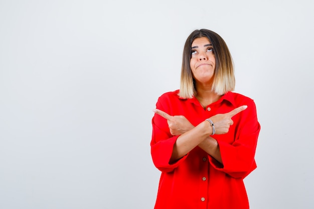 Jonge dame die naar beide kanten wijst in een rood oversized shirt en besluiteloos kijkt, vooraanzicht.