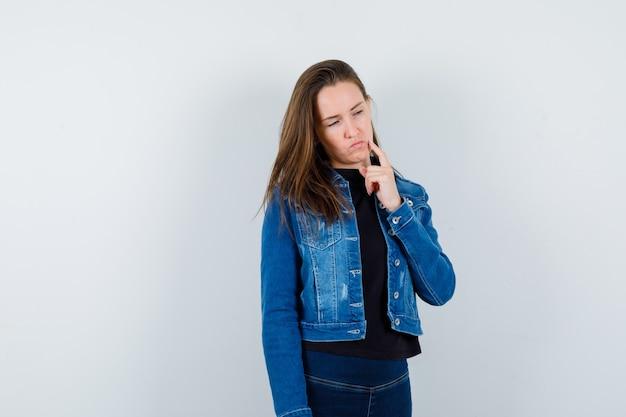 Jonge dame die naar beneden kijkt terwijl ze in een blouse denkt en aarzelend kijkt. vooraanzicht.