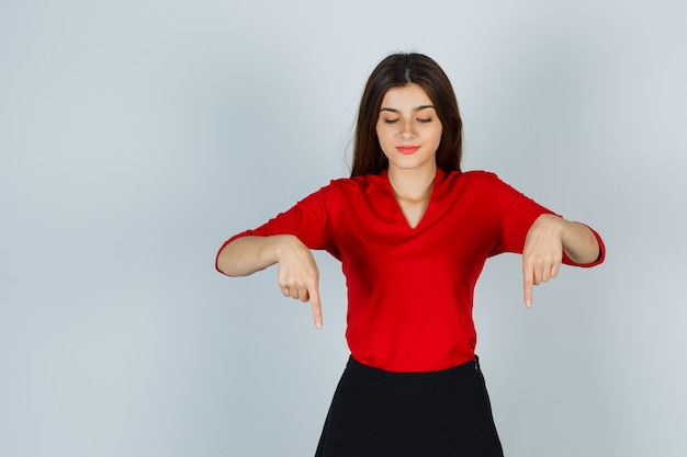 Jonge dame die naar beneden wijst in rode blouse, rok en er zelfverzekerd uitziet
