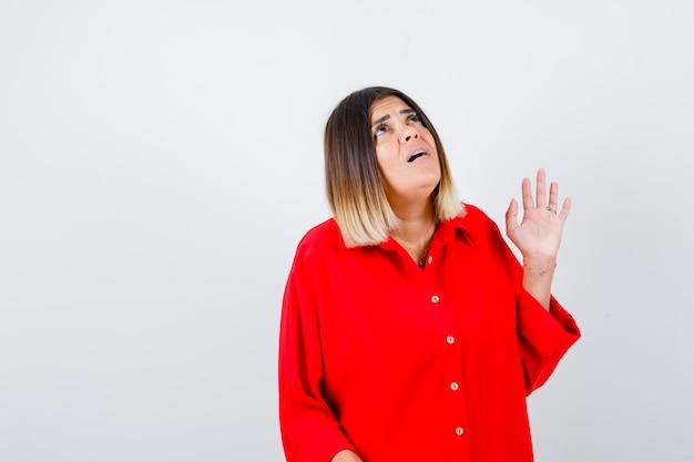 Jonge dame die naar boven kijkt in een rood oversized shirt en er angstig uitziet. vooraanzicht.