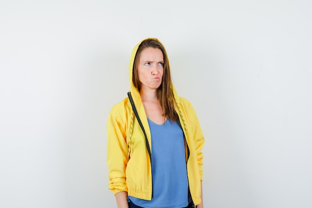 Jonge dame die naar boven kijkt terwijl ze fronsend in t-shirt, jasje kijkt en aarzelend kijkt
