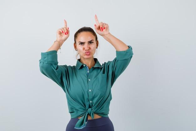 Jonge dame die naar boven wijst, lippen pruilt in een groen shirt en er zelfverzekerd uitziet. vooraanzicht.
