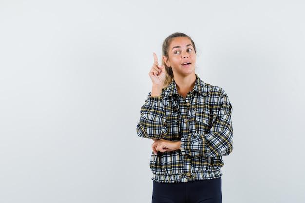 Jonge dame die naar boven wijst, uitstekend idee vindt in shirt, korte broek en er vrolijk uitziet, vooraanzicht.