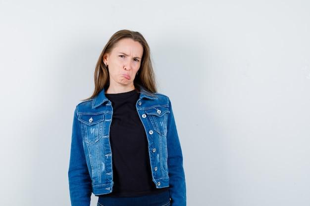 Jonge dame die naar de camera kijkt terwijl ze fronst in blouse, jas en beledigd kijkt, vooraanzicht.