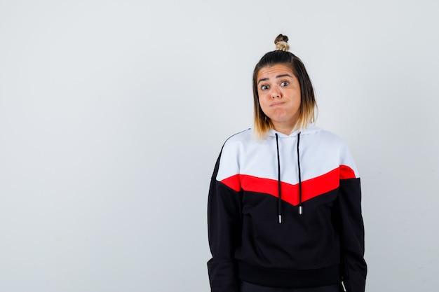 Jonge dame die naar de camera kijkt terwijl ze op de wangen blaast in een hoodietrui en er grappig uitziet.