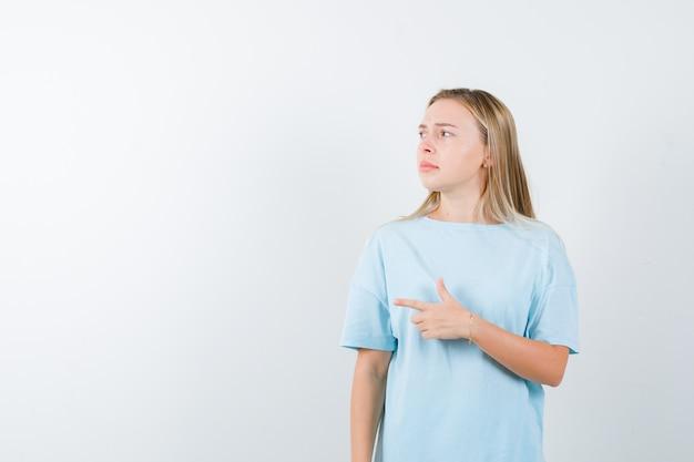 Jonge dame die naar de linkerkant in t-shirt wijst en aarzelend kijkt. vooraanzicht.