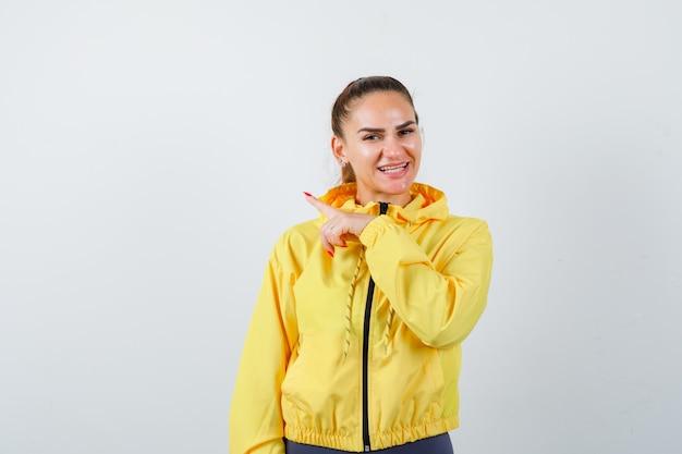 Jonge dame die naar de linkerkant wijst in een gele jas en er vrolijk uitziet. vooraanzicht.