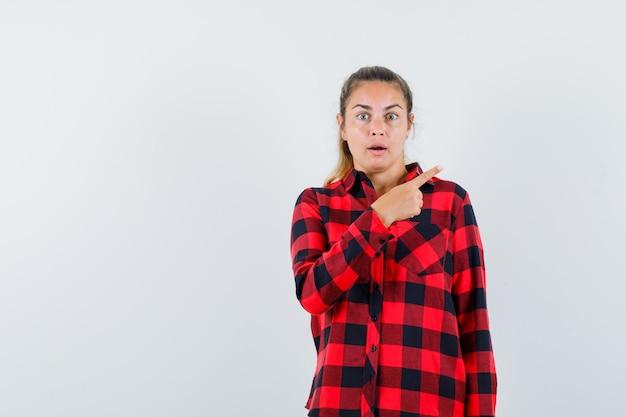 Jonge dame die naar de rechterbovenhoek in een geruit overhemd wijst en verbaasd kijkt