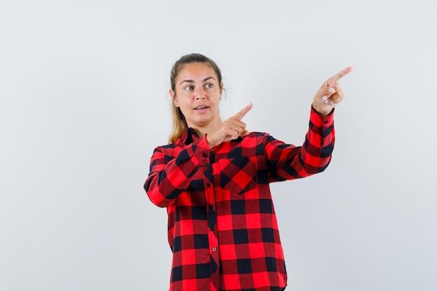 Jonge dame die naar de rechterbovenhoek in geruit overhemd wijst en gefocust kijkt