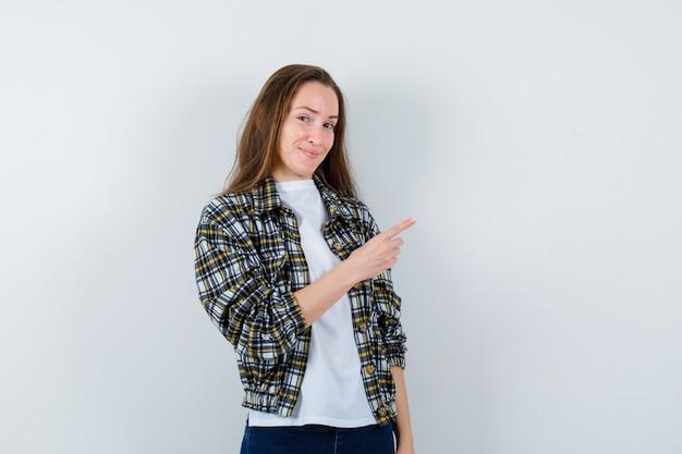 Jonge dame die naar de rechterbovenhoek in t-shirt, jasje wijst en zelfverzekerd kijkt. vooraanzicht.