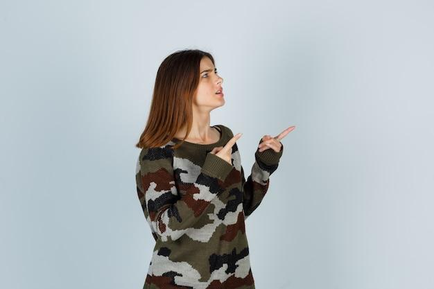 Jonge dame die naar de rechterbovenhoek in trui wijst en gefocust kijkt