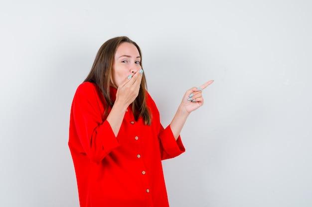 Jonge dame die naar de rechterbovenhoek wijst, de hand op de mond houdt in een rode blouse en er geamuseerd uitziet. vooraanzicht.