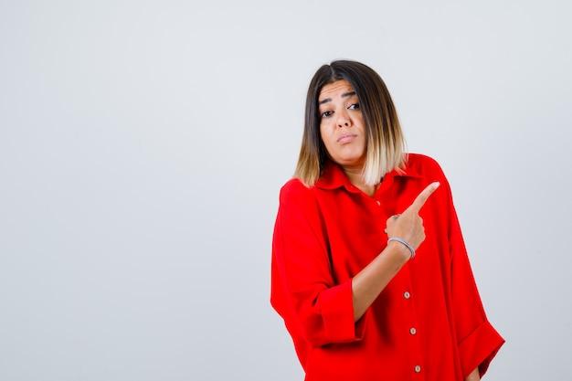 Jonge dame die naar de rechterbovenhoek wijst in een rood oversized shirt en besluiteloos kijkt, vooraanzicht.