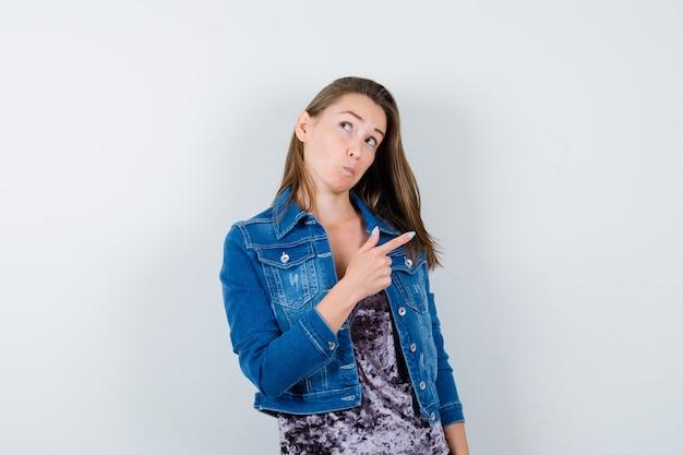 Jonge dame die naar de rechterkant wijst in blouse, spijkerjasje en er attent uitziet, vooraanzicht.