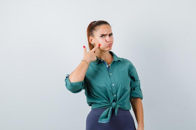 Jonge dame die naar haar gezwollen wang in een groen shirt wijst en er ontevreden uitziet, vooraanzicht.
