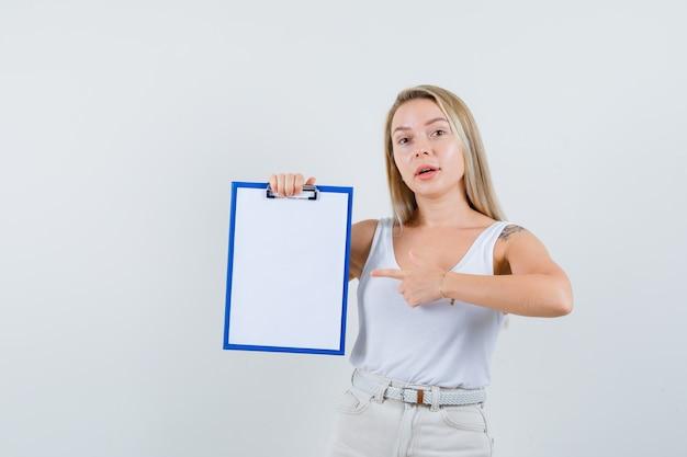 Jonge dame die naar leeg klembord in witte blouse wijst en gericht kijkt