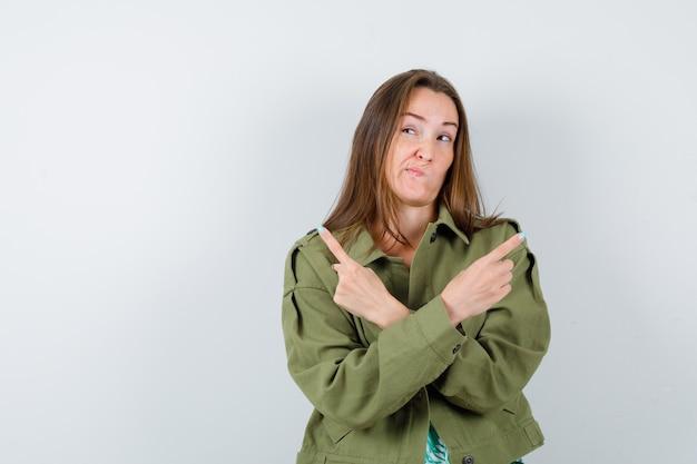 Jonge dame die naar rechts en links wijst in een groen jasje en besluiteloos kijkt, vooraanzicht.