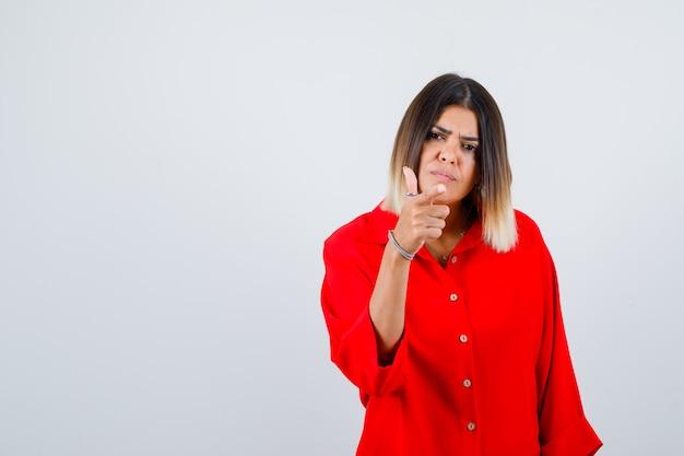 Jonge dame die naar voren wijst in een rood oversized shirt en er serieus uitziet, vooraanzicht.