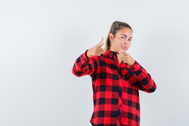 Jonge dame die naar voren wijst in geruit overhemd en er zelfverzekerd uitziet
