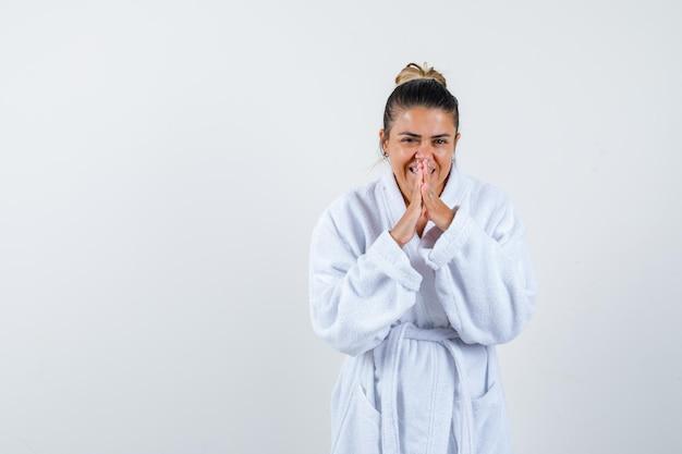 Jonge dame die namaste-gebaar in badjas toont en er hoopvol uitziet
