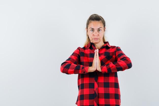 Jonge dame die namaste-gebaar in geruit overhemd toont en zelfverzekerd kijkt