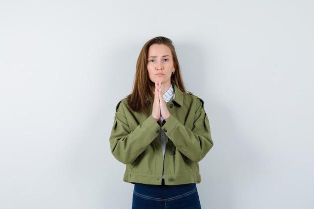 Jonge dame die namaste-gebaar in shirt, jas toont en er hoopvol uitziet, vooraanzicht.