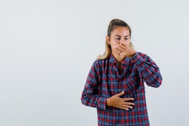 Jonge dame die neus knijpt als gevolg van slechte geur in geruit overhemd en walgt, vooraanzicht.