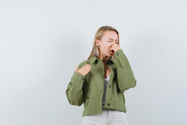 Jonge dame die neus knijpt als gevolg van slechte geur in jas, broek en walgt, vooraanzicht.