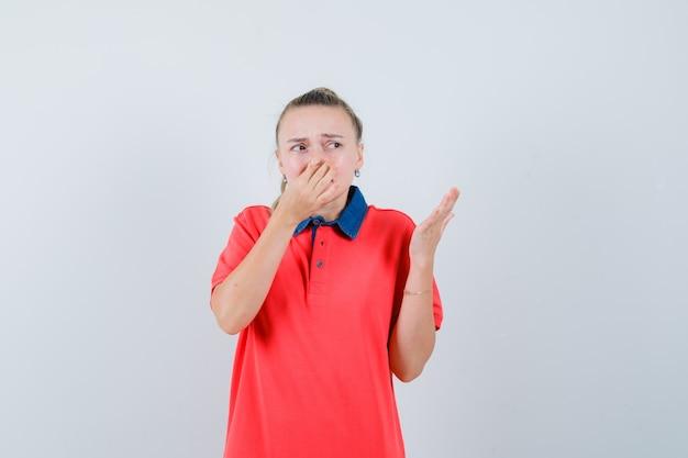 Jonge dame die neus knijpt als gevolg van stank in t-shirt en walgt op zoek