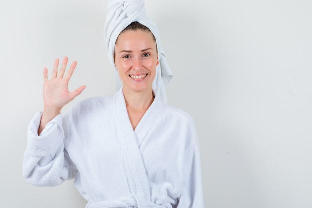 Jonge dame die nummer vijf in witte badjas, handdoek toont en vreugdevol, vooraanzicht kijkt.