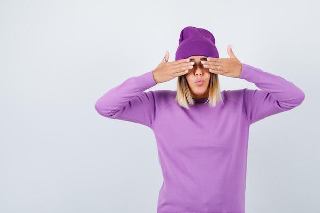 Jonge dame die ogen bedekt met handen in paarse trui, muts en er geamuseerd uitziet, vooraanzicht.