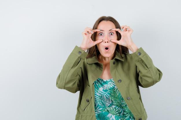 Jonge dame die ogen opent met vingers in blouse, jas en verbaasd kijkt. vooraanzicht.