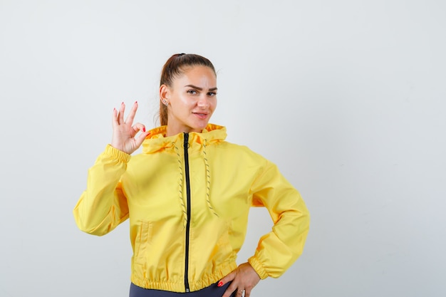 Jonge dame die ok gebaar in geel jasje toont en tevreden kijkt, vooraanzicht.