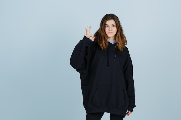 Jonge dame die ok gebaar in overmaatse hoodie, broek toont en er zelfverzekerd uitziet, vooraanzicht.
