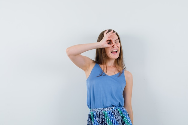 Jonge dame die ok gebaar op oog in hemd, rok toont en vrolijk kijkt. vooraanzicht.