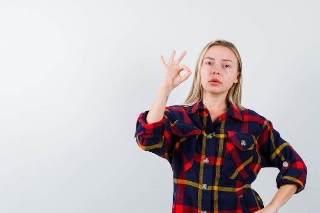 Jonge dame die ok gebaar toont terwijl hand op taille in geruit overhemd wordt gehouden en er zelfverzekerd uitziet, vooraanzicht.