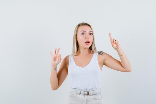 Jonge dame die ok gebaar toont terwijl omhoog in witte blouse wijst en tevreden kijkt
