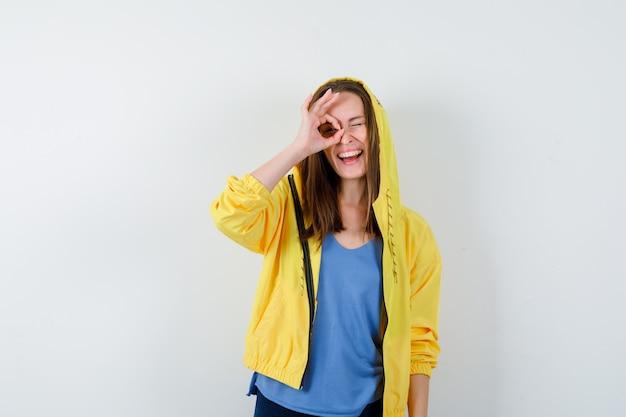 Jonge dame die ok teken op oog in t-shirt, jasje toont en blij kijkt, vooraanzicht.