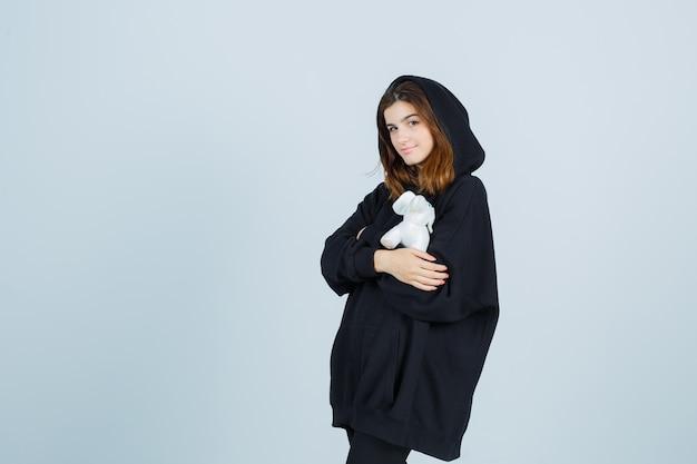 Jonge dame die olifantspeelgoed op borst in oversized hoodie, broek houdt en er schattig uitziet, vooraanzicht.