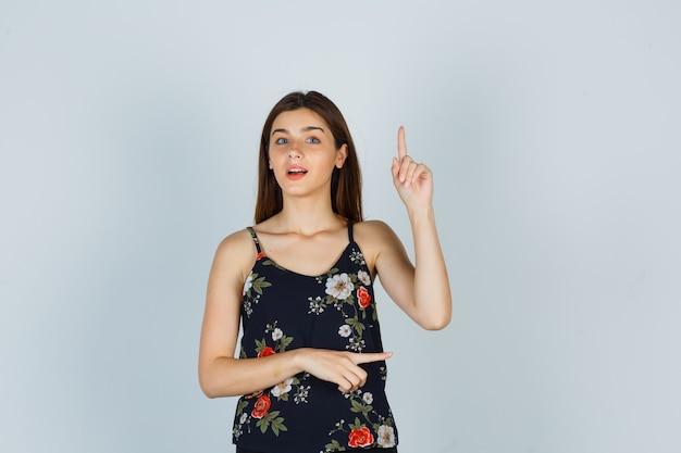 Jonge dame die omhoog en rechts in blouse wijst en verwonderd kijkt. vooraanzicht.