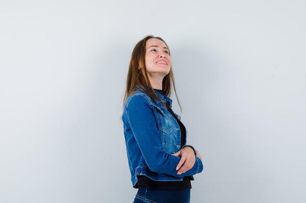 Jonge dame die omhoog kijkt in blouse, jas en er dromerig uitziet, vooraanzicht.