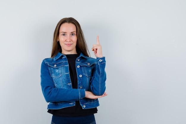 Jonge dame die omhoog wijst in blouse, jas en er zelfverzekerd uitziet, vooraanzicht.