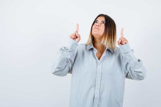 Jonge dame die omhoog wijst in een oversized shirt en er attent uitziet. vooraanzicht.